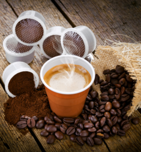 Cup of coffee surrounded by coffee pods and beans