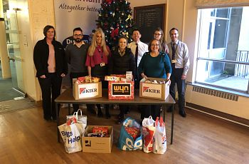Image of staff behind Christmas tree with food hampers